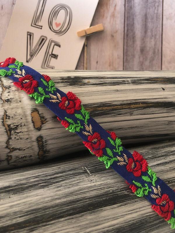 gargantilla azul con flores rojas y hojas verdes producto